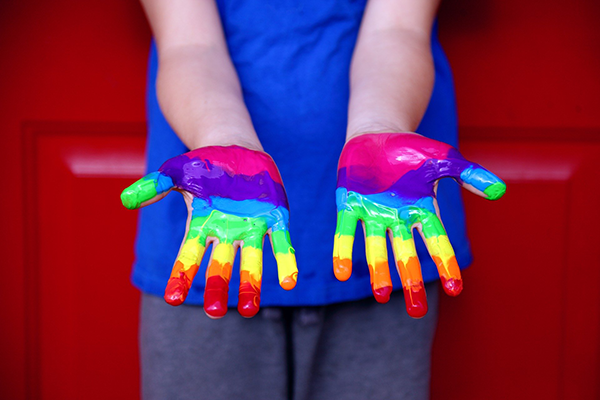 child with rainbow paint on hands