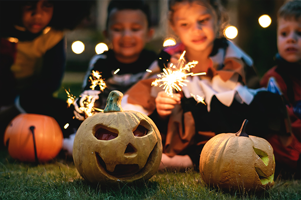 halloween pumpkins and sparklers held by children