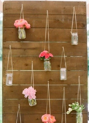flowers in jars hanging on pallets